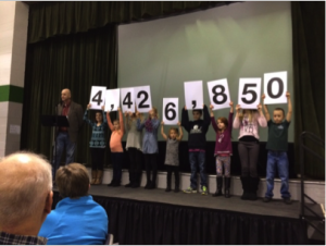 Students help announce the pledge total.
