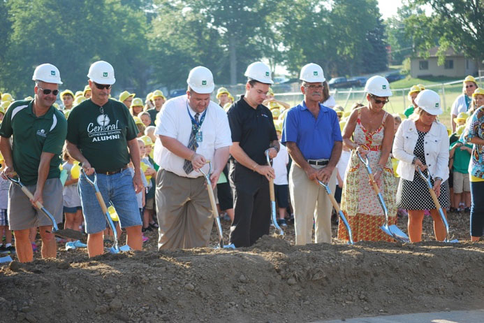 Director of Advancement John Weber center in tie and members of the school board and capital campaign team break ground